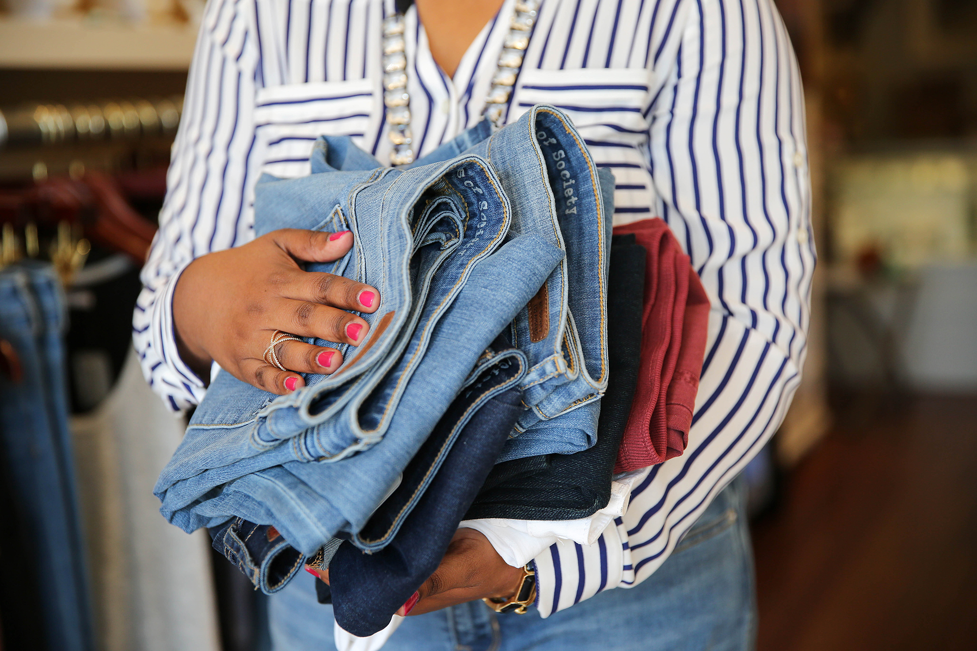 Neepa holding stack of jeans
